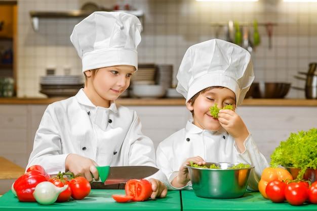 Śmieszne chłopcy szczęśliwy gotowanie w kuchni restauracji