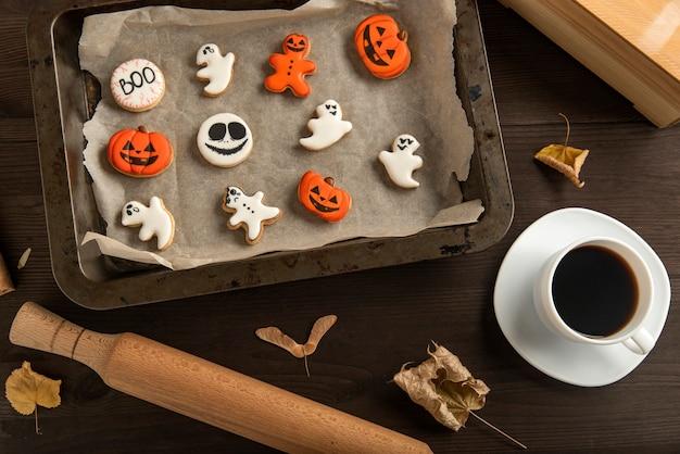 Śmieszne ciasteczka na halloween leżą w formie do pieczenia. duchy i ciastko z dyni. filiżanka czarnej kawy. pyszne słodycze