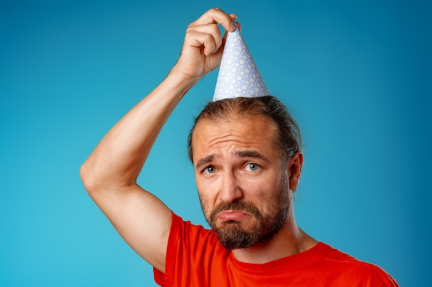 Śmieszne długowłosy brodaty mężczyzna w partii stożka na niebieskim tle