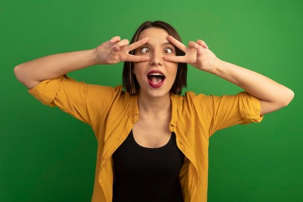 Śmieszne dość kaukaski kobieta mruży oczy i gesty znak ręką zwycięstwa z dwiema rękami na zielono