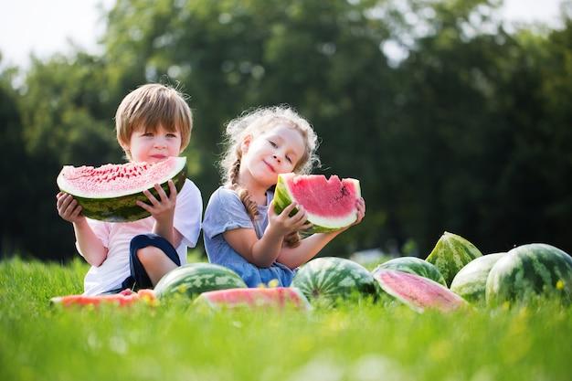 Śmieszne dzieci jedzą arbuza na świeżym powietrzu. zdrowa żywność latem.