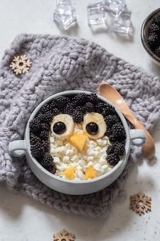 Śmieszne dzieci pingwin owsianka śniadaniowa ze świeżymi jagodami