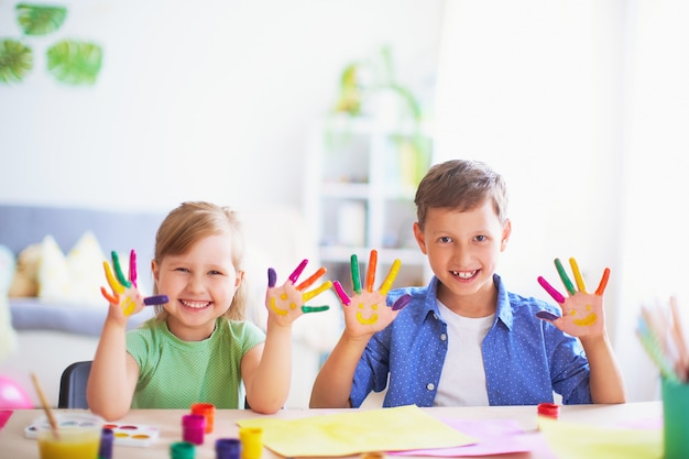 Śmieszne dzieci pokazują dłoniom pomalowaną farbę.