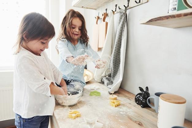 Śmieszne dzieci przygotowują ciasto. przyjaciele z przedszkola uczą się gotować z mąki w białej kuchni.