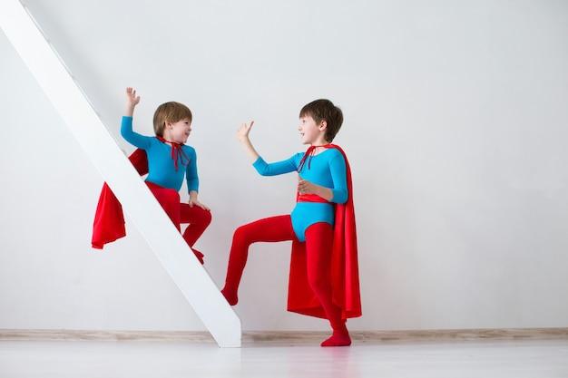 Śmieszne dzieci superbohaterów bawiące się superbohaterów na białym tle