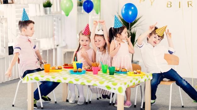 Śmieszne dzieci w kolorowych czapkach