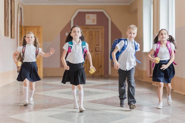 Śmieszne dzieci z jabłkami w szkolnym korytarzu