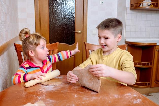 Śmieszne dzieciaki pieczą ciasteczka w kuchni. szczęśliwa rodzina.