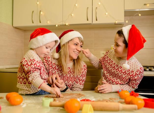Śmieszne dzieciaki przygotowują ciasto, pieką pierniki w kuchni w zimowy dzień. śmieszne dzieci i mama pieczą ciasteczka na boże narodzenie.
