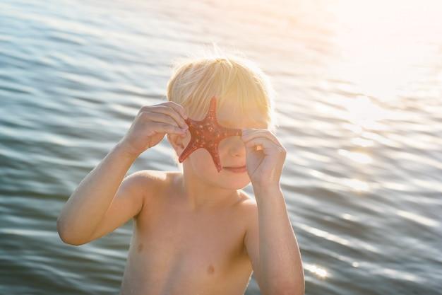 Śmieszne dziecko blondynem bawi się rozgwiazda. wakacje nad morzem z dziećmi