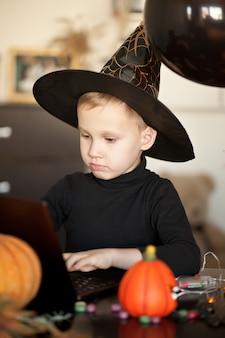 Śmieszne dziecko chłopiec w złym stroju na halloween za pomocą notebooka laptopa cyfrowego tabletu. dzwoń online do znajomych lub rodziców.