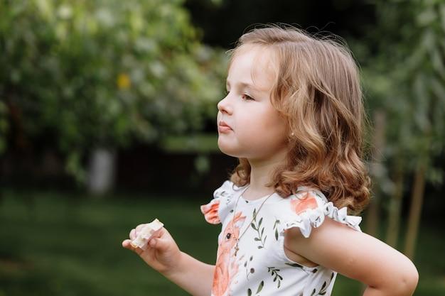 Śmieszne dziecko dziewczynka jedzenie kanapki na zewnątrz.
