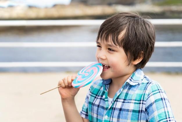 Śmieszne dziecko jedzące lizaka, szczęśliwy mały chłopiec trzymający duży cukier
