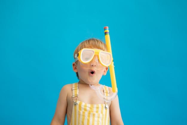 Śmieszne dziecko nosi maskę do nurkowania przed niebieską ścianą.