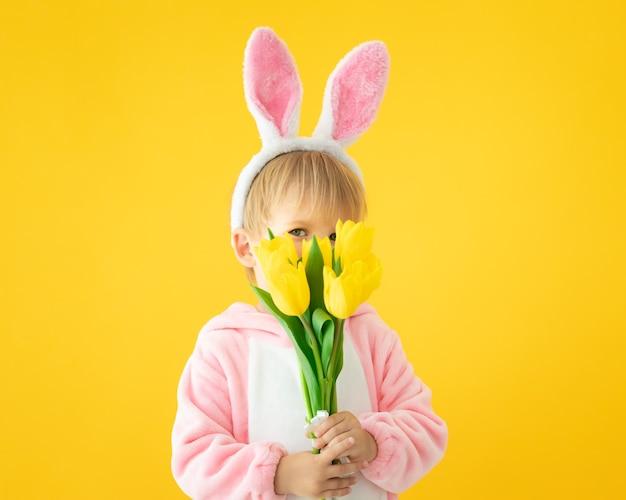 Śmieszne dziecko nosi uszy królika wielkanocnego i trzyma bukiet tulipanów na żółtej ścianie.