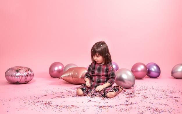 Śmieszne dziecko siedzi na różowym tle. mała dziewczynka ma zabawę z balonami i confetti
