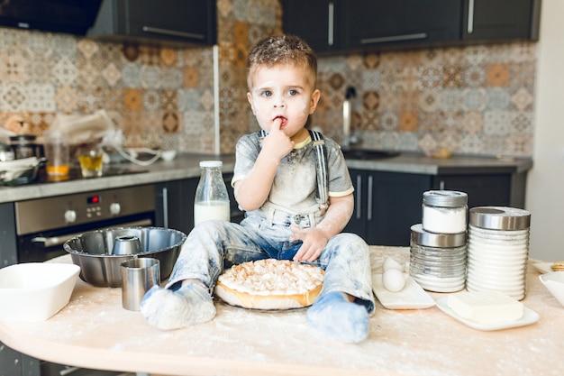 Śmieszne dziecko siedzi na stole w kuchni akustycznej, bawi się mąką i degustuje ciasto.