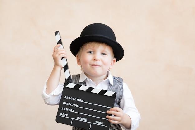 Śmieszne dziecko trzyma deska klakier. szczęśliwe dziecko, zabawy w domu. koncepcja kina retro