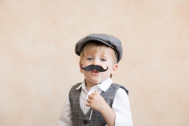 Śmieszne dziecko trzyma fałszywe wąsy. szczęśliwe dziecko bawiące się w domu