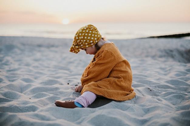 Śmieszne dziecko w orientalnej sukience siedzi na piasku na plaży i bawi się piaskiem