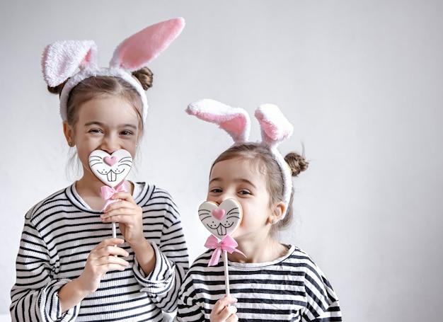Śmieszne dziewczynki z wielkanocnymi uszami na głowach i wielkanocnymi pierniczkami na patykach.