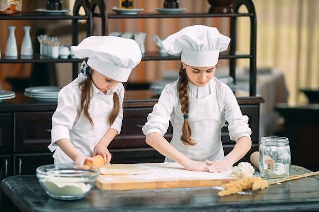 Śmieszne dziewczyny dzieci przygotowują ciasto w kuchni.
