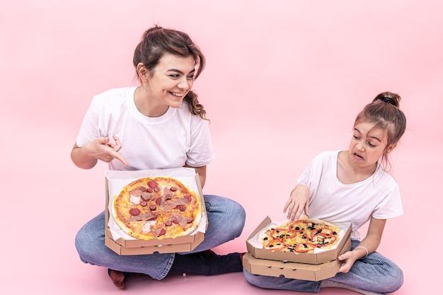 Śmieszne dziewczyny z pizzą w pudełkach do dostawy na różowym tle