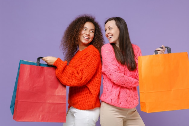 Śmieszne europejskie afrykańskie amerykańskie kobiety przyjaciele w swetry z dzianiny na białym tle na fioletowej ścianie fioletowy. koncepcja stylu życia ludzi trzymaj torbę z zakupami po zakupach, patrząc na siebie.