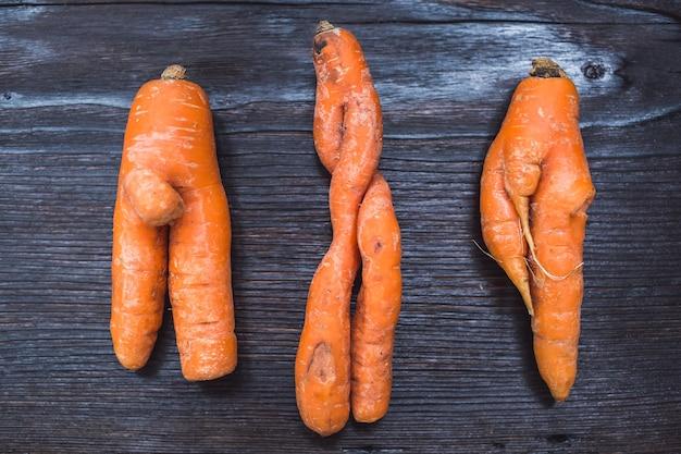 Śmieszne formy marchewki na powierzchni ciemnej deski.