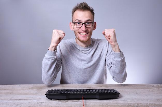 Śmieszne frajerem młody biznesmen, mężczyzna pracujący na komputerze. pisanie na klawiaturze programisty w okularach przed komputerem.