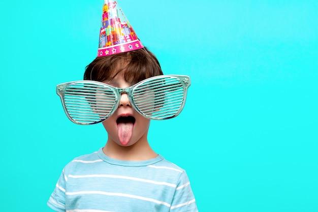 Śmieszne grymasy chłopca w dużych okularach i świątecznym kapeluszu. koncepcja wakacji dla dzieci