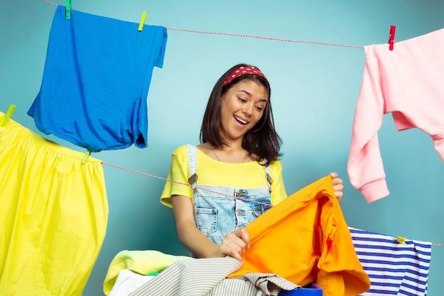 Śmieszne i piękne gospodyni domowej na białym tle na niebieskim tle. młoda kobieta kaukaski otoczona przez umyte ubrania. życie domowe, jasne dzieła sztuki, koncepcja sprzątania. składanie prania.