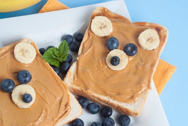Śmieszne jedzenie dla dzieci. tosty z masłem orzechowym w kształcie uszu.