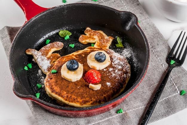 Śmieszne jedzenie na boże narodzenie. naleśnik dla dzieci ozdobiony jak renifer, z gorącą czekoladą z pianką, biały stół