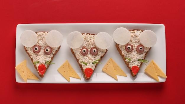 Śmieszne kanapki dla dzieci w kształcie ślicznych myszek z serem, jajkami i paluszkami krabowymi na czerwonym tle, pomysł na sztukę jedzenia, widok z góry