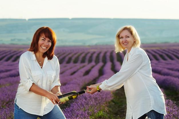 Śmieszne kobiety przyjaciele z butelką wina w lawendowym polu