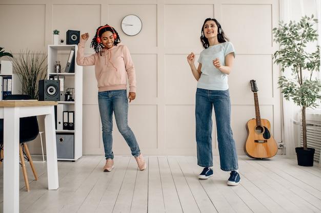 Śmieszne kobiety tańczą i słuchają muzyki w domu. ładne dziewczyny w słuchawkach odpoczywają w pokoju, miłośnicy dźwięku odpoczywają na kanapie, koleżanki spędzają razem wolny czas