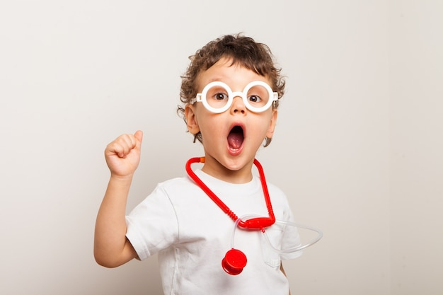 Śmieszne kręcone dziecko w okularach ze stetoskopem na szyi gra lekarza. zbliżenie dziecka, chłopca pokazującego zdziwienie i trzymającego palec w górze. pomysł.