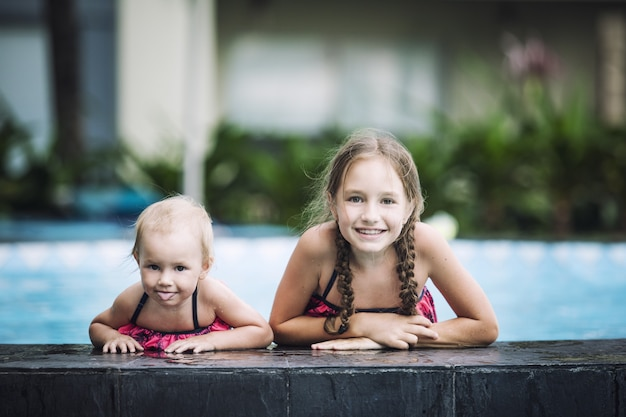 Śmieszne małe dzieci dziewczyny uśmiechają się i pływają w odkrytym basenie piękne i szczęśliwe