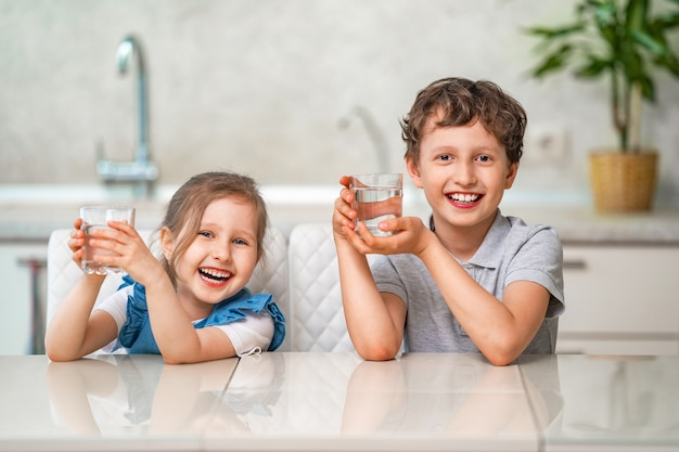 Śmieszne małe dzieci piją wodę w kuchni w domu