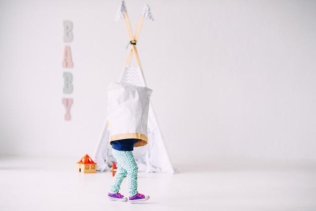 Śmieszne małe dziecko biegające po jasnym pokoju z papierową torbą na głowie na dziecięcym wigwamie