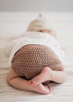 Śmieszne małe dziecko śpi na białe prześcieradła