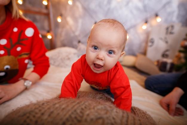 Śmieszne małe dziecko w czerwonym swetrze. noworoczne zdjęcie dziecka. dziecko uczy się czołgać