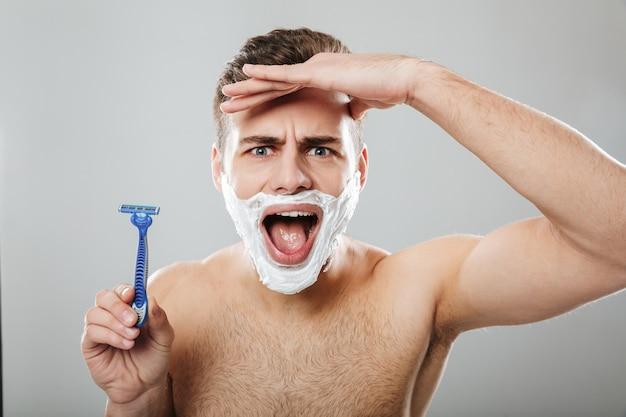 Śmieszne mimiki zarośnięty mężczyzna robi poranną procedurę z brzytwą i kremem na twarzy na szarej ścianie