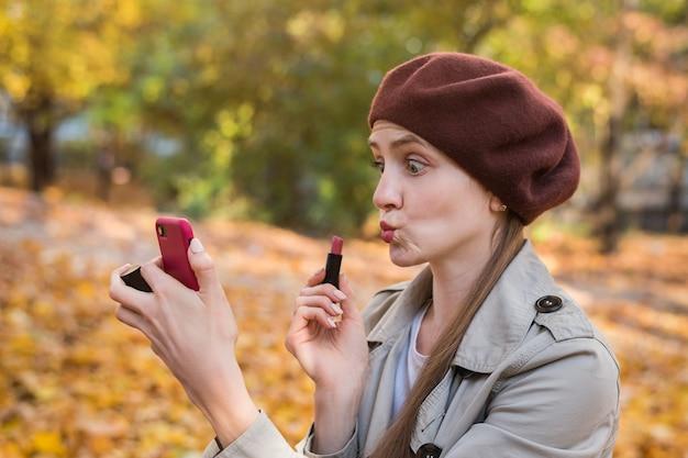 Śmieszne młoda kobieta trzyma szminkę w jej ręce i sprawia, że selfie.