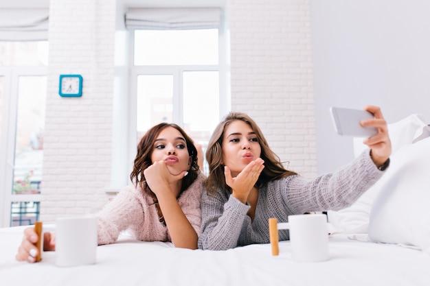 Śmieszne młode kobiety w przytulnych miękkich swetrach co selfie portret na łóżku. radosne dziewczyny dobrze się bawią, przesyłają buziaka, piją kawę, przyjaciele, szczęśliwy poranek.