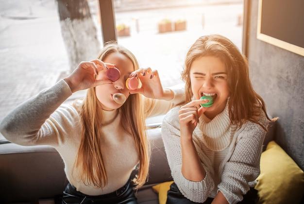 Śmieszne młode kobiety zakrywają oczy macarons. pozują przed kamerą. brunetka gryzie kawałek makaronika. bawią się dobrze.