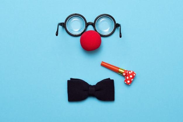 Śmieszne okulary, czerwony nos klauna i krawat leżą na kolorowym tle, jak twarz