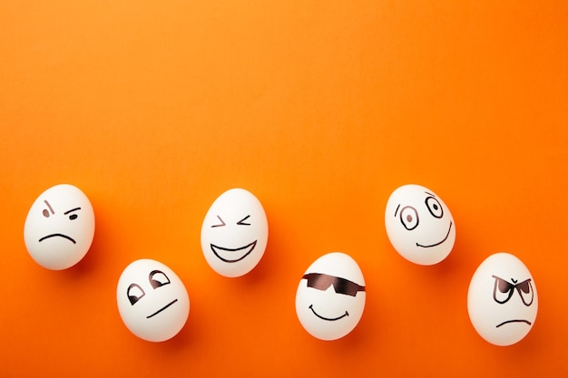 Śmieszne pisanki z różnymi emocjami na twarzy na pomarańczowym tle.
