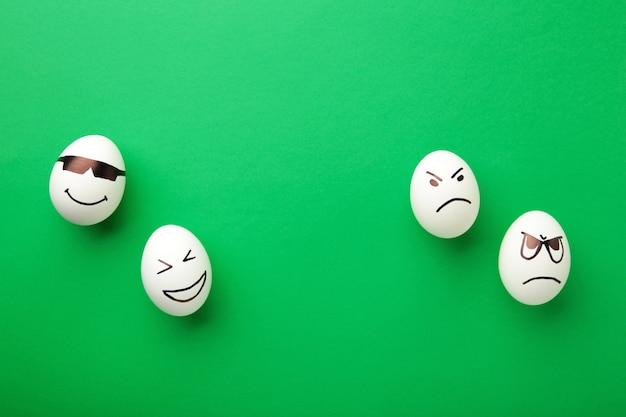 Śmieszne pisanki z różnymi emocjami na twarzy na zielonym tle.
